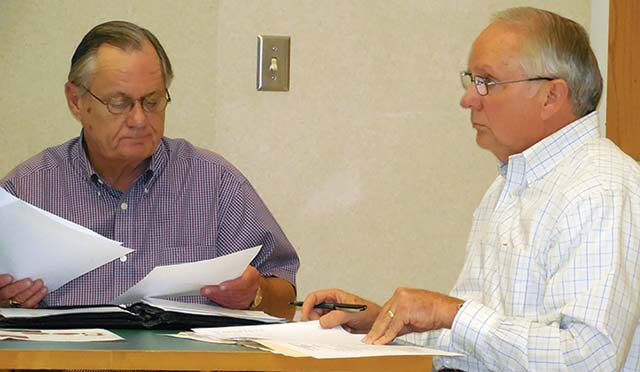 Newly elected HCHD Board Vice President Larry Christopher (left) and newly appointed HCHD Director Dr. Perry Ramsey, MD (right) are shown as Dick Murchison (not pictured), investment officer, presents the September  financial report. (Photo by Lynda Jones)