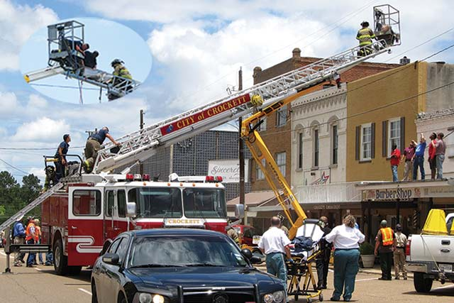 Photos By Kim Duhon After an insurance adjuster from Frankston made contact with high power electrical lines in downtown Crockett Wednesday afternoon, June 4, the Crockett Volunteer Fire Department sped to the scene with Ladder 1 and successfully brought the man down.  The large view above shows the yellow arm of the elevated cage that contained the man.  The inset shows three CVFD firefighters stablizing the man for transfer from the bucket down the ladder.  ETMC EMS paramedics were waiting below with a stretcher.  (Photos by Kim Duhon)